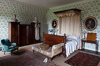 An elaborately turned bed is just one among several pieces of antique furniture in one of the bedrooms