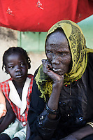 An elderly woman with scarification marks outside a referendum centre where people can register themselves for the upcoming referendum on independence. Together with many other IDPs (Internally Displaced Persons) she has just returned from Khartoum, the capital in the north, to South Sudan. Many Sudanese, who fled Sudan during the civil war, are returning home, mainly to participate in the upcoming referendum in January 2011, when South Sudan will vote on its independence.