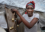 """A survivor of the January 2010 earthquake stands in the doorway of her """"tent"""" home in a camp in the Bobin neighborhood of Port-au-Prince, Haiti."""