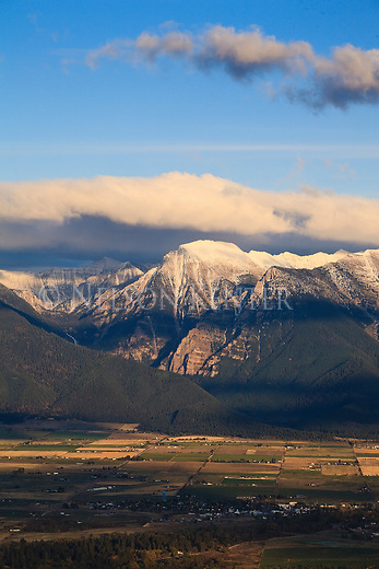 Late day sunlight on the Mission Mountains and clouds near St. Ignatius, Montana