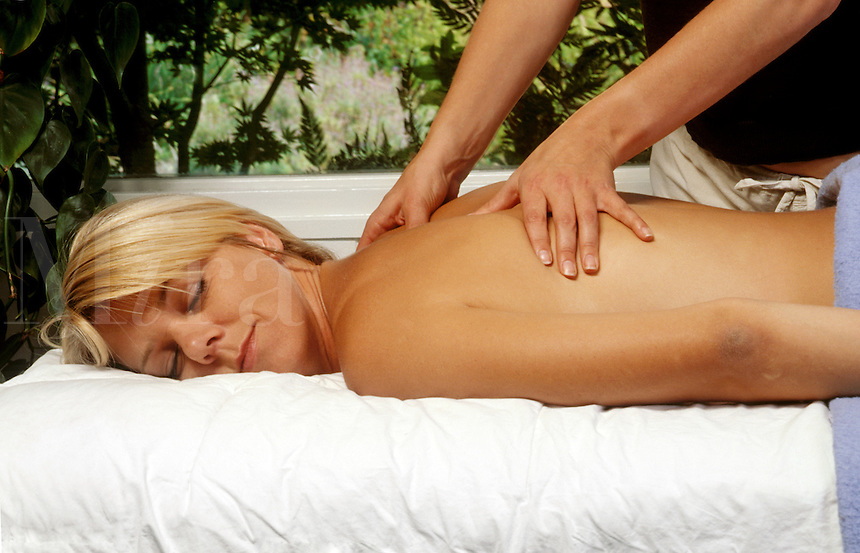 A MASSAGE THERAPIST works on a female client.