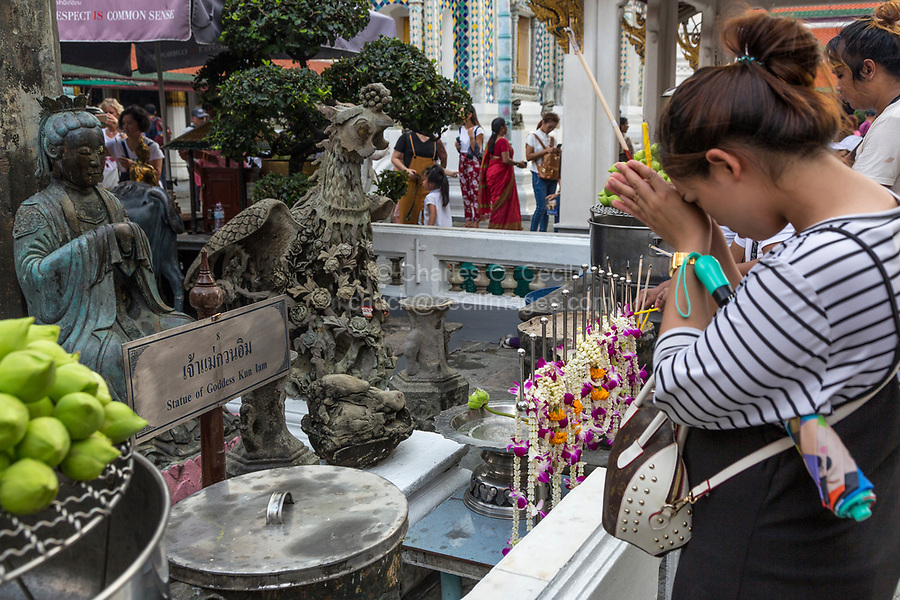 Bangkok, Thailand.  Worshiper Praying to Goddess of Mercy Kun Iam, at the Royal Grand Palace.