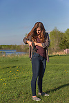 Young woman places her pistol in a conceal carry waistband.