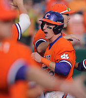 First baseman Jon McGibbon (12) of the Clemson Tigers is congratulated in a game against the University of Alabama-Birmingham on Feb. 17, 2012, at Doug Kingsmore Stadium in Clemson, South Carolina. UAB won 2-1. (Tom Priddy/Four Seam Images)