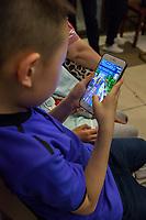 Suzhou, Jiangsu, China.  Young Chinese Boy Playing a Game on his Mobile Phone.