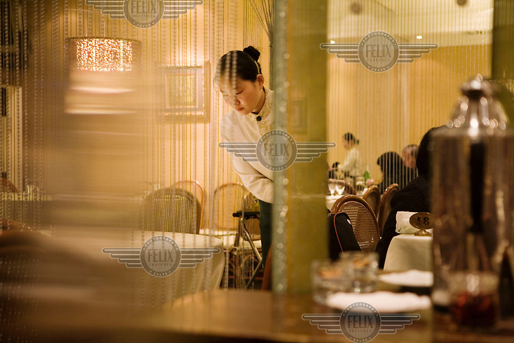 Waitress clears tables in a restaurant. The average wage of a waitress is 600 RMB (80 USD) per month with food and lodging.
