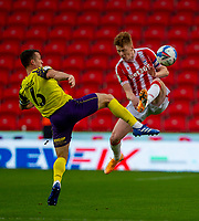 21st November 2020; Bet365 Stadium, Stoke, Staffordshire, England; English Football League Championship Football, Stoke City versus Huddersfield Town; Jonathan Hogg of Huddersfield Town and Sam Clucas of Stoke City jump for the ball