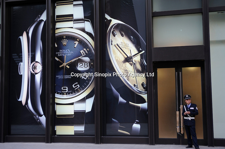 A security guard stands in ftont of a huge advertisement of ROLEX at Shin Kong Place, which is one of the most luxurious shopping centers in Beijing, having successfully attracted 938 international class brands, they also boast the largest Gucci flagship store in Asia..