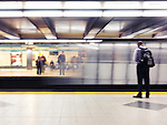 People standing on a subway platform waiting for the arriving train. Artistic motion blur. Bloor station, TTC, Toronto, Ontario, Canada.
