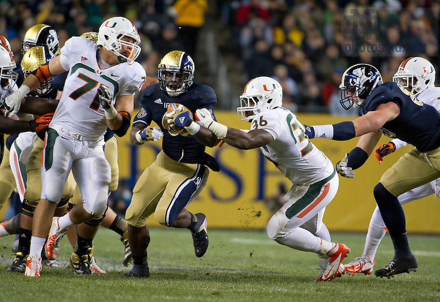 Oct. 6, 2012; Running back Theo Riddick gains yardage for a first down as Miami linebacker Gionni Paul moves in for the tackle during the second quarter of the Shamrock Series at Soldier Field in Chicago. Photo by Barbara Johnston/University of Notre Dame..