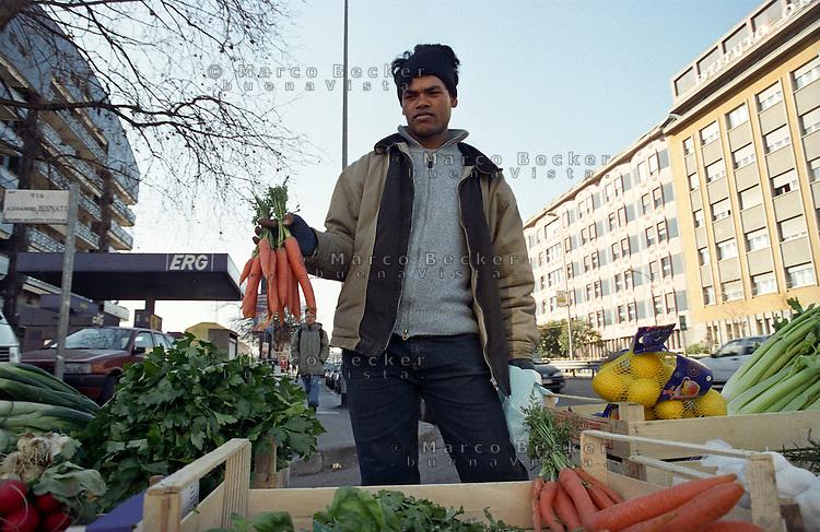 Milano, mercato rionale al quartiere Bruzzano, periferia nord. Ragazzo del Bangladesh vende verdura --- Milan, local market at Bruzzano district, north periphery. Bangladeshi boy sells vegetables