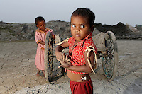 Two children in the grounds of a brick factory, in the Malancha district of eastern Kolkata. As their parents work nearby, children often play in the area, exposing them to harmful materials and waste produced in the industrial process. India. November, 2013