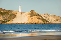 Surfing at Castlepoint with lighthouse, Hawke's Bay, North Island, New Zealand, NZ