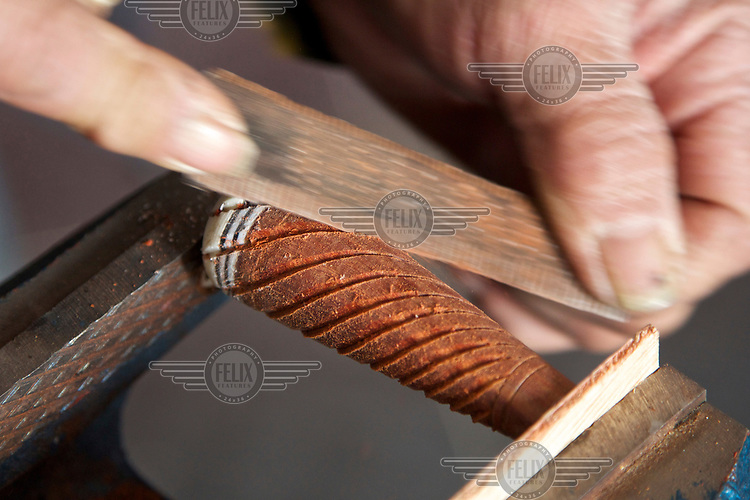 A craftsman makes a musical instrument for a performer at the Ma Jie folk festival. <br /> <br /> For centuries farmers in Henan have gathered during Chinese New Year in the region's wheat fields to listen to bards singing and recounting old tales. <br /> <br /> Now storytellers come from all over China to attend the annual festival where large crowds gather to watch the best performers.