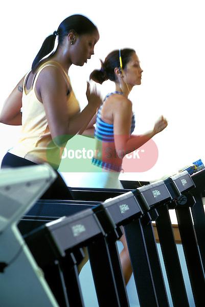 young women running on treadmills in health club