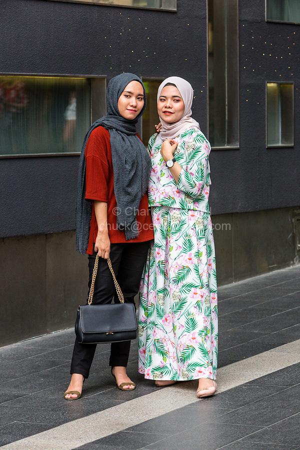 Young Malaysian Women Posing for a Photo, Traditional Dress vs. Casual Western Style, Pavilion Mall, Bukit Bintang, Kuala Lumpur, Malaysia.
