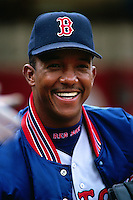 OAKLAND, CA - Pedro Martinez of the Boston Red Sox smiles while watching the game in the dugout during a game against the Oakland Athletics at the Oakland Coliseum in Oakland, California in 1999. Photo by Brad Mangin