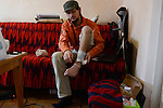 """Mykola, 24, from Kiev sits in his apartment in a Soviet-style flat near the outskirts of Kiev, Ukraine on April 4, 2014.  Mykola was shot in the left leg near his ankle at 4:30am on February 19, 2014, while filming and walking up steps in the middle of Maidan Square.<br /> <br /> """"They aimed at journalists and those with cameras to start clearing Maidan.  I personally don't know who did this.  But I know it was these special Alpha troops led by Asaveluk and I know he has not been relieved of his duty.  I was there from the very first day, the night November 21st.  We were aiming to change the rules of the game.  What I see now is a change of power and authorities without changes to the system.  If the change will not come, we will have a third Maidan and it will be more serious."""""""