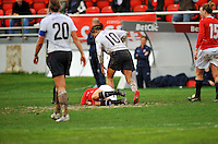 Carli Lloyd offers a muddied hand to assist a Norwegian defender. The USA defeated Norway 2-1 at Olhao Stadium on February 26, 2010 at the Algarve Cup.