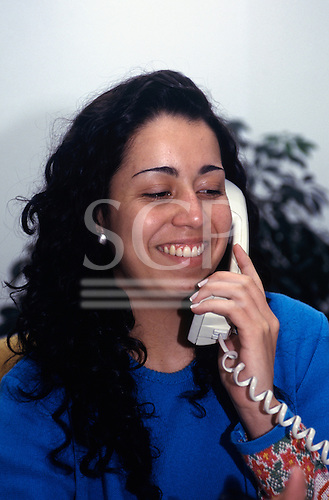 """Rio Grande do Sul, Brazil. Smiling girl with long hair talking on the phone - """"Fasolo""""(factory for leather goods)."""