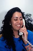 "Rio Grande do Sul, Brazil. Smiling girl with long hair talking on the phone - ""Fasolo""(factory for leather goods)."