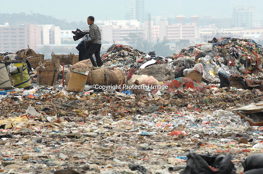 """The landfill of Tangxia in Guangdong Province, China. As well as some domestic waste the landfill mostly comprises of waste, such as offcuts discarded from shoe and textile factories discarded in the Tangxia area. Tangxia is a heavily polluted town and home of a factory  that makes trainers for the """"green"""" and """"socially concious"""" company Wornagain."""