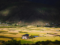 After the road descent from Dochula Pass, sunlight bursts through heavy rainclouds illuminating a lone farmhouse and the lush valley below Dechan Hill, Thinleygang, Bhutan