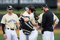 Wake Forest Demon Deacons relief pitcher John McCarren (45) gets a hug from catcher Ben Breazeale (39) as he comes out of the game against the Pitt Panthers at David F. Couch Ballpark on May 20, 2017 in Winston-Salem, North Carolina. The Demon Deacons defeated the Panthers 14-4.  (Brian Westerholt/Four Seam Images)