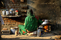 A sex worker prepares her evening meal by the side of the highway in Bharatpur, Rajasthan. Traditionally the Bedia caste see their women enter the sex trade from the age of 13-14...