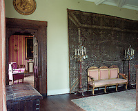An ornately carved door frame surrounds the entrance to the drawing room and a faded tapestry hangs behind a canape in the hall