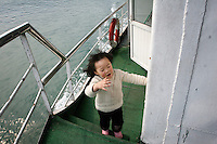 CHINA. Hubei Province. A girl on a boat passing through the 3 Gorges.  The flooding of the three Gorges, by damming the Yangtze near the town of YiChang, has remained a controversial subject due to the negative environmental consequences and the displacement of millions of people in the flood plain. The Yangtze River however is reported to be at its lowest level in 150 years as a result of a country-wide drought. It is China's longest river and the third longest in the world. Originating in Tibet, the river flows for 3,964 miles (6,380km) through central China into the East China Sea at Shanghai.  2008.