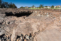 Petroglyphs and cave shelter at the Waikoloa Petroglyph Field, with the King's Course golf course and condos in the distance, Big Island.
