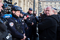 French Defence Minister Jean-Yves Le Drian (L) and Interior Minister Bruno Le Roux speak to police at the Louvre Museum as emergency security measures continue ahead of New Year's eve celebrations in and around the French capital, in Paris, France, December 30, 2016.