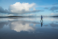 Reflection of woman walking on Traigh Lingeigh beach, North Uist, Outer Hebrides, Scotland
