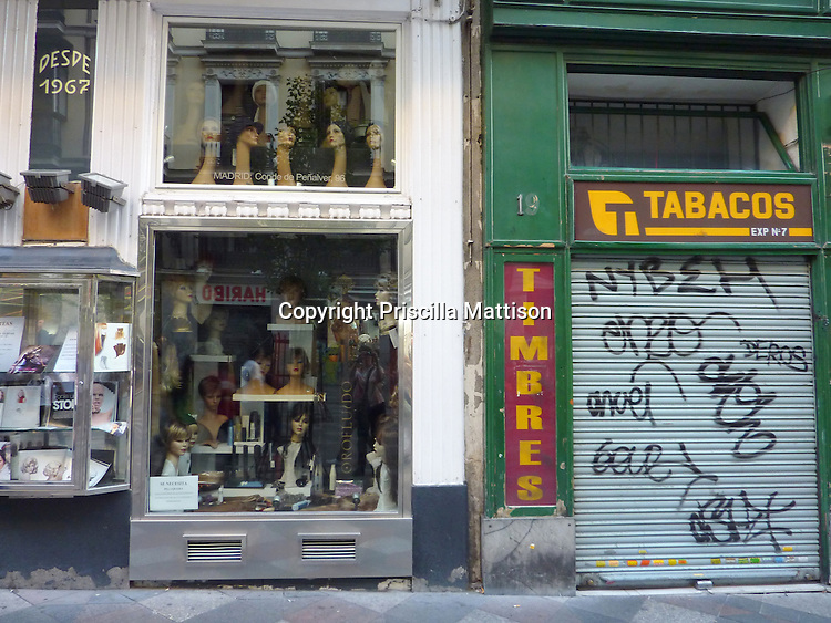 Madrid, Spain - October 15, 2011:  A wig shop stands next to a tobacco storefront.