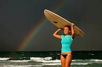 A momentary break in a Florida storm arcs a brilliant rainbow over a surfer having her photo taken. Rainbow actually appear (not PhotoShop).