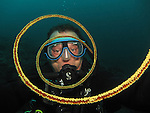 Kenting, Taiwan -- Diver seen through the spirals of a whip coral.<br /> <br /> This is a self-portrait. Had I not been too preoccupied with taking this shot I might have actually spotted the tiny shrimp that can be seen on the coral in the foreground during the dive.