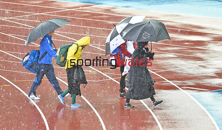 Wales' Sally Peake, right, shelters under an umbrella during a down pour of rain as she waits for the women's pole vault competition to start<br /> <br /> Photographer Chris Vaughan/CameraSport<br /> <br /> 20th Commonwealth Games - Day 10 - Saturday 2nd August 2014 - Athletics - Hampden Park - Glasgow - UK
