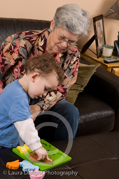 2 year old toddler boy at home with grandmother playing with puzzle encouraged to play with it vertical Caucasian she takes care of him when parents work