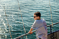 A Boy Scout looks out to sea while deep-sea fishing about 15 miles off the South Carolina coast near Huntington Beach State Park. Image is model released.