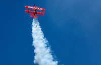 Sean Tucker flies his bright Orange Oracle Challenger through the blue sky over the crowds at Dayton Ohio