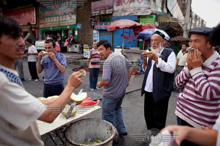Uighur men eat melon in the Uighur district of Urumqi.