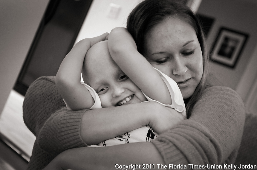 """Kelly.Jordan@jacksonville.com--021712--Eight-year-old Madison """"Maddie"""" Thomas of Atlantic Beach gets a big hug from her mom Angela Thomas as they spend time together at home Friday February 17, 2012. Maddie has been battling neuroblastoma, a common and aggressive cranial tumor among children and has taken a turn for the worse and doctors are advising an expensive course of treatment. Friends of her parents Matt and Angela Thomas are planning a fundraiser to help that will take place Sunday, Feb. 26th.(The Florida Times-Union, Kelly Jordan)"""
