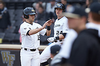 Logan Harvey (15) of the Wake Forest Demon Deacons high fives his teammates after scoring a run against the Sacred Heart Pioneers at David F. Couch Ballpark on February 15, 2019 in  Winston-Salem, North Carolina.  The Demon Deacons defeated the Pioneers 14-1. (Brian Westerholt/Four Seam Images)