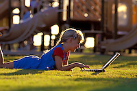 Young girl usea a laptop computer at the park.