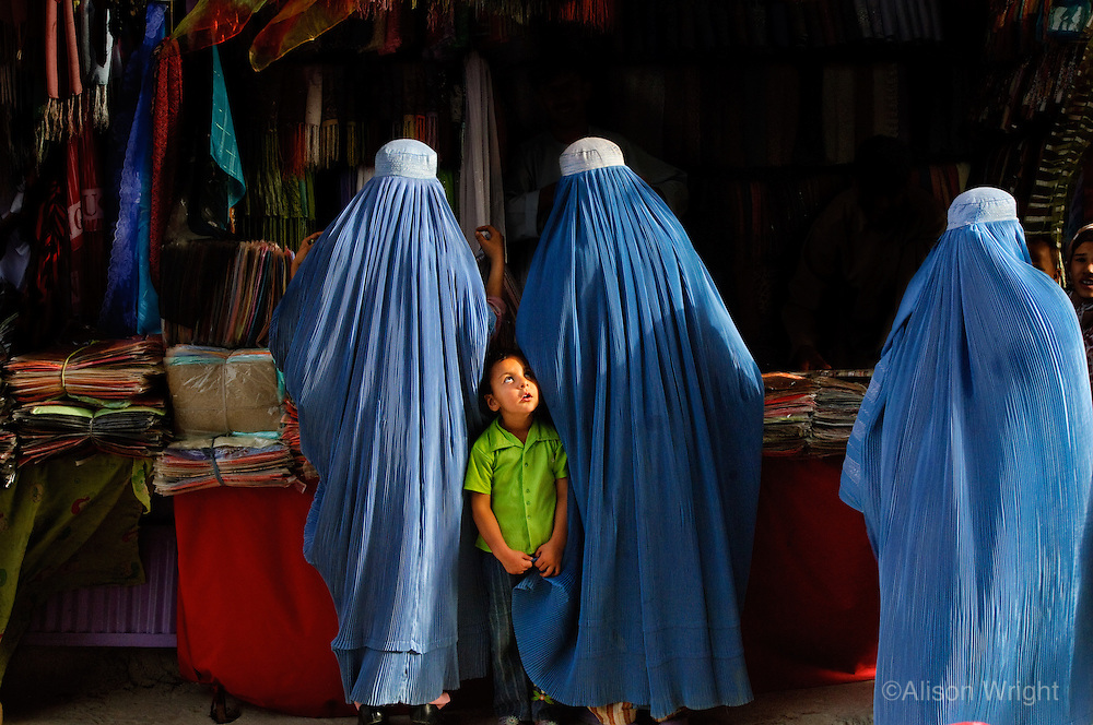 Are you my mother?  Mazar-E-Sharif, Afghanistan.<br /> I watched with amusement as this boy grabbed the hems of a few burkas before zoning in on his mother in a busy market place. Getting lost and dealing with the boredom of shopping with your mother seems to be universal for little boys the world over.