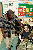 MR / Albany, NY.Langan School at Center for Disability Services .Ungraded private school which serves individuals with multiple disabilities.Teaching assistant (African-American) talks with a child. Boy: 11, cerebral palsy, expressive and receptive language delays.MR: Bro12; Wes2.© Ellen B. Senisi