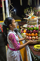Bali, Indonesia.  Young Hindu Woman Placing an Offering at the Temple in Hopes of a Good Rice Harvest.  Pura Dalem Temple, Dlod Blungbang Village.