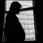 Pregnant woman looks through a window at Trellick Tower, West London (posed by model).....