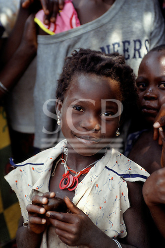 Zambia. Smiling young girl in a ragged dress.